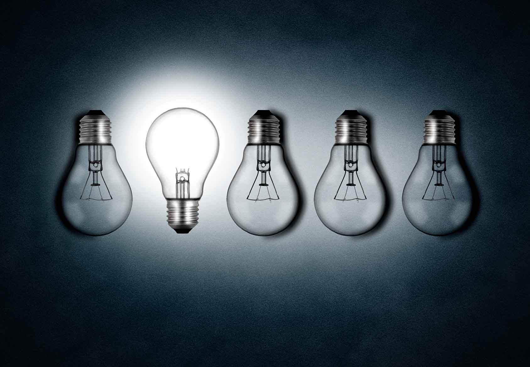 Illuminated lightbulb amid dim bulbs - creativity and innovation concept