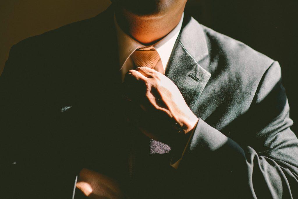 Man adjusting tie looking smart
